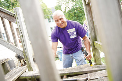 Volunteer working on porch with purple shirt